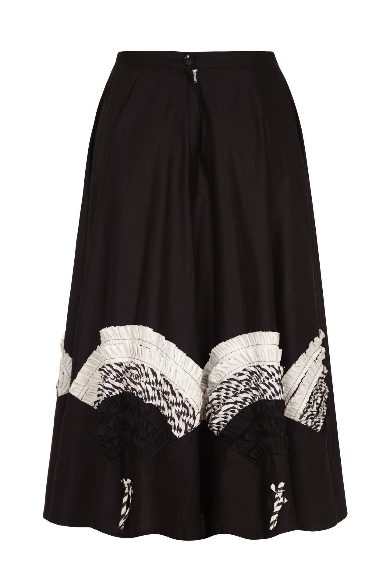 Fun 1950s full black cotton circle skirt with lovely monochrome pleated applique all around the hem in fan motifs.  This piece fastens at the back with a zip and button and is in excellent condition.