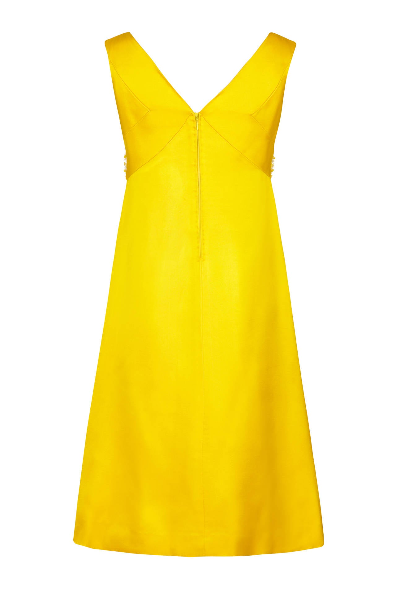 Stunning late 1960s French Couture yellow silk A line mini dress.  This piece features unusual white and yellow floral 3D beading and rhinestones around the V neckline and pretty panelling around the bust.  Unfitted around the waist it fastens at