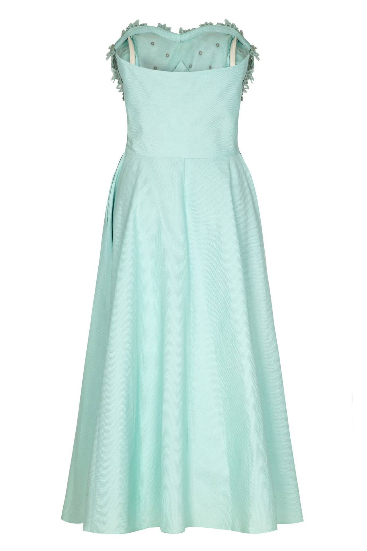 Late 1950s American pale blue textured cotton strapless dress.  This is a great piece and features pretty 3D floral and rhinestone applique to the bust.  It is boned in the bodice for extra support, has layers of net in the calf length skirt for