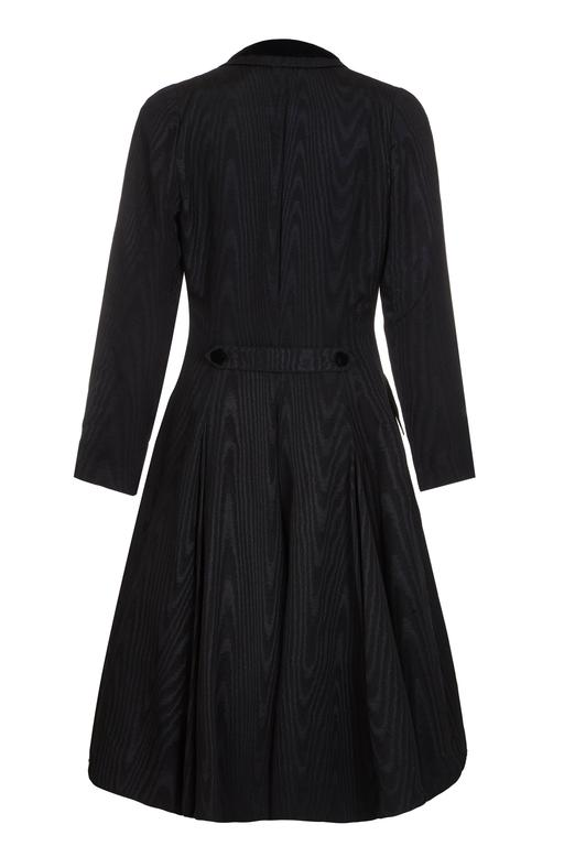 Very theatrical 1980s Louis Feraud black moire (watered) fabric dress in the style of a Victorian riding coat.  Beautifully made and very fitted, the double breasted design features velvet buttons and trim on the neckline of the collar and pockets.