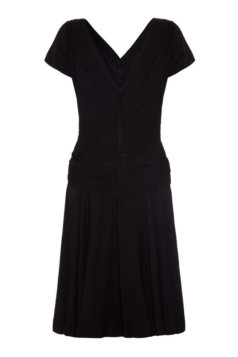 Great little black dress from American designer Ceil Chapman.  Featuring pretty cross over and ruching detail to the front and a sexy low neckline to the back this is the perfect party dress! The short sleeves add a little extra cover and the full
