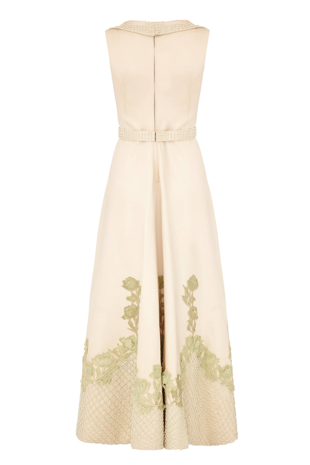 Exceptional vintage 1950s custom made heavy cream silk gown with pale green floral appliques and pearl beaded lattice work.  This sleeveless, waisted dress features a deep V neckline with collar and comes with original matching beaded belt.  It is