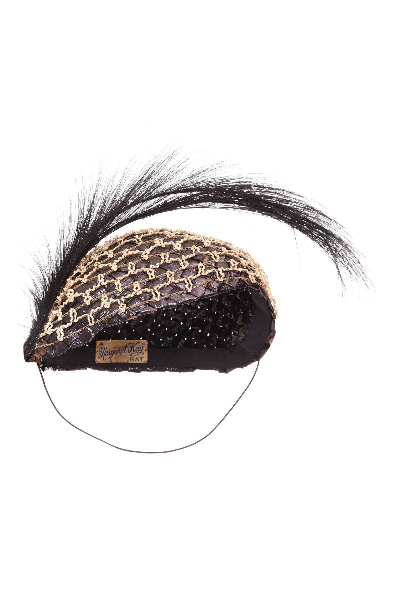 Very rare, original 1920s flapper hat made from coated black woven raffia. Additional antique two-tone cream lattice overlay to one half of the hat, topped with a black hair spray.  Original label reads