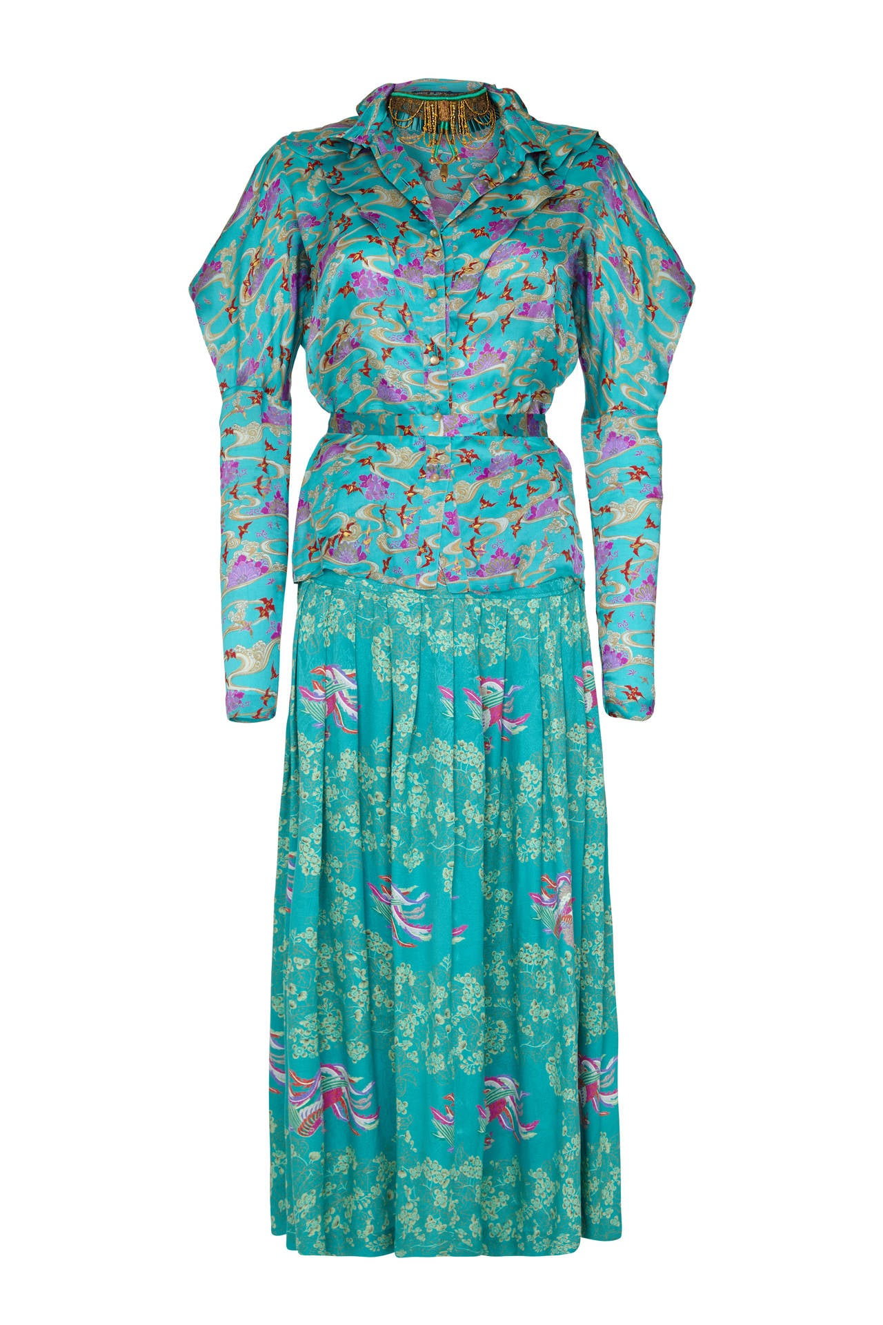 Extraordinary turquoise silk set from Ungaro with oriental style print consisting of structured blouse, full-length skirt, beaded necklace, oversized scarf with gold tassels and matching tie belt.  The blouse features pearl buttons to fasten at the