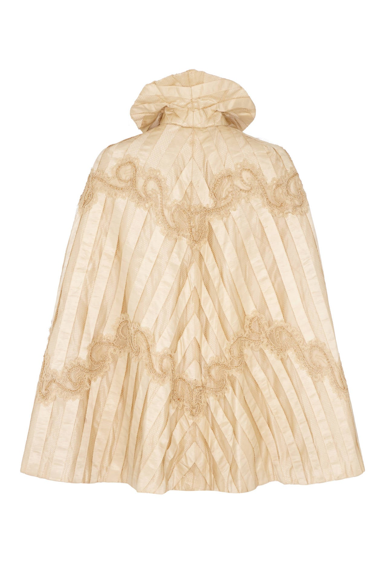 Beautiful cream silk cape dating from the 1880s consisting of stripes of silk ribbon and silk netting with an intricate corded and lace applique.  There are no makers labels but this is an outstanding piece and was most likely originally a wedding