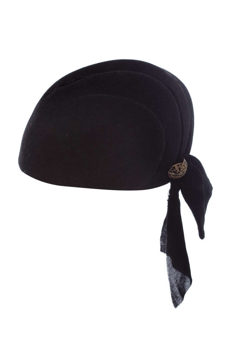Early 1930s, possibly late 1920s moulded scallop shaped black felt hat. This lovely piece features a pretty black silk velvet trim and matching velvet ribbon bow detail to one side with a filigree brooch. A really good size to fit most people and in