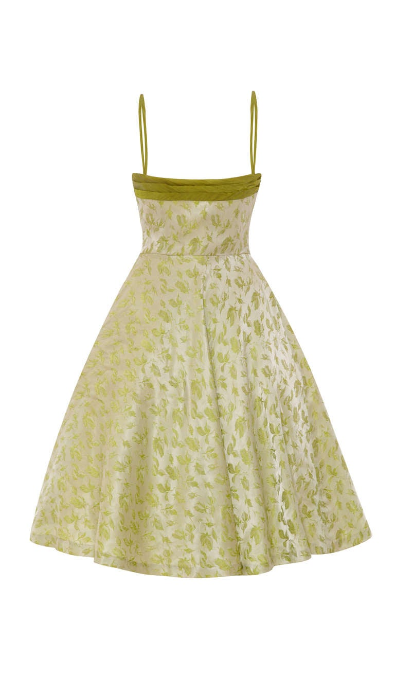 Absolutely amazing 1950's dress in green silk brocade with scattered rosebuds on the skirt.  The asymmetrical bodice has a pleated coordinating green organza section around the top with matching spaghetti straps and is lined and boned for extra