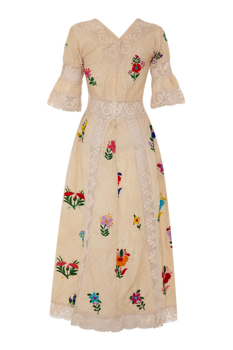 Stunning original 1970s cream cotton wedding dress with typical Mexican bright and bold floral embroidery and pin tucks throughout.  This full-length dress also features a pretty and wide cream lace trim around the neckline, waist, sleeves and skirt