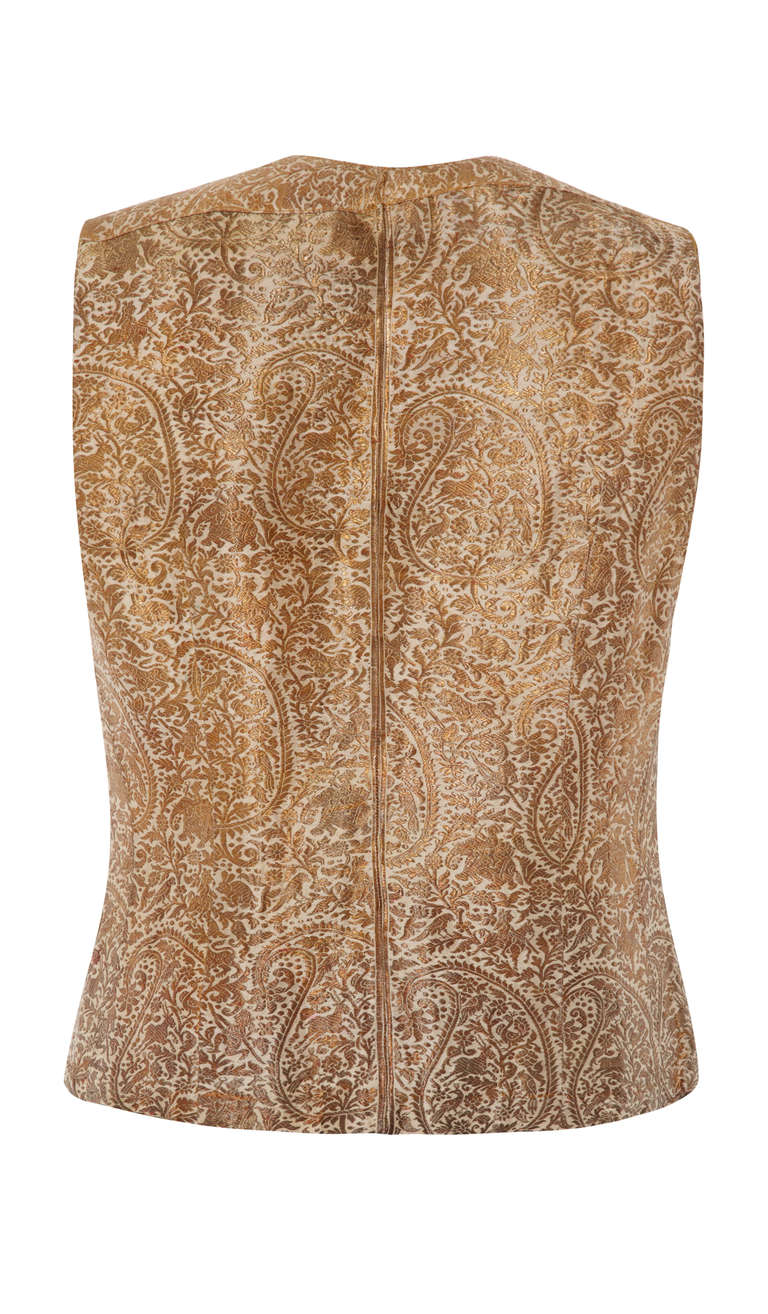 A stunning little Indian waistcoat in a gorgeous real gold thread brocade.  This piece features an intricate pattern of paisley, floral and animals embroidered on a cream background. It is fully lined in a cream silk lining and fastens at the front