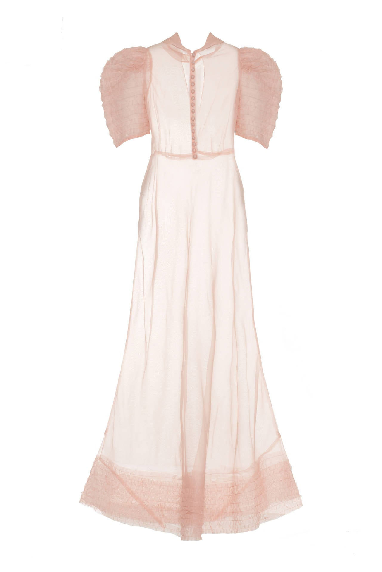 This beautiful pale pink organza floor length tea gown has exaggerated puff sleeves which feature rows of stitched ruffled organza.  It also has corresponding rows of stitched ruffles on the hem. The A-line dress has a lovely peter pan collar and 16
