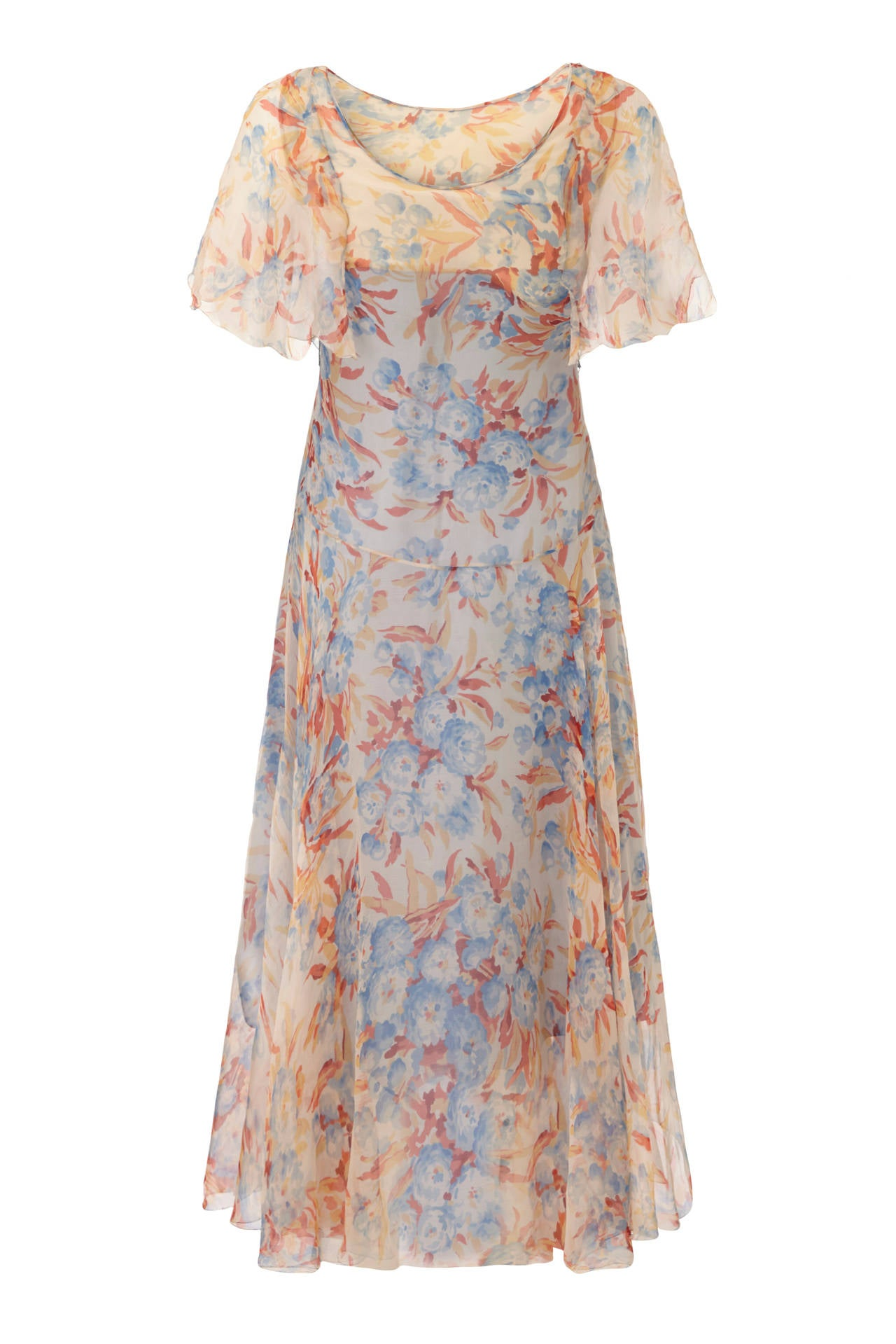 Gorgeous floaty peach silk chiffon original 1920s dress with pretty blue and red floral print. This piece features cape style sleeves with scalloped edge, dropped waist and poppers to fasten at the side.  It is in excellent condition and is lined in