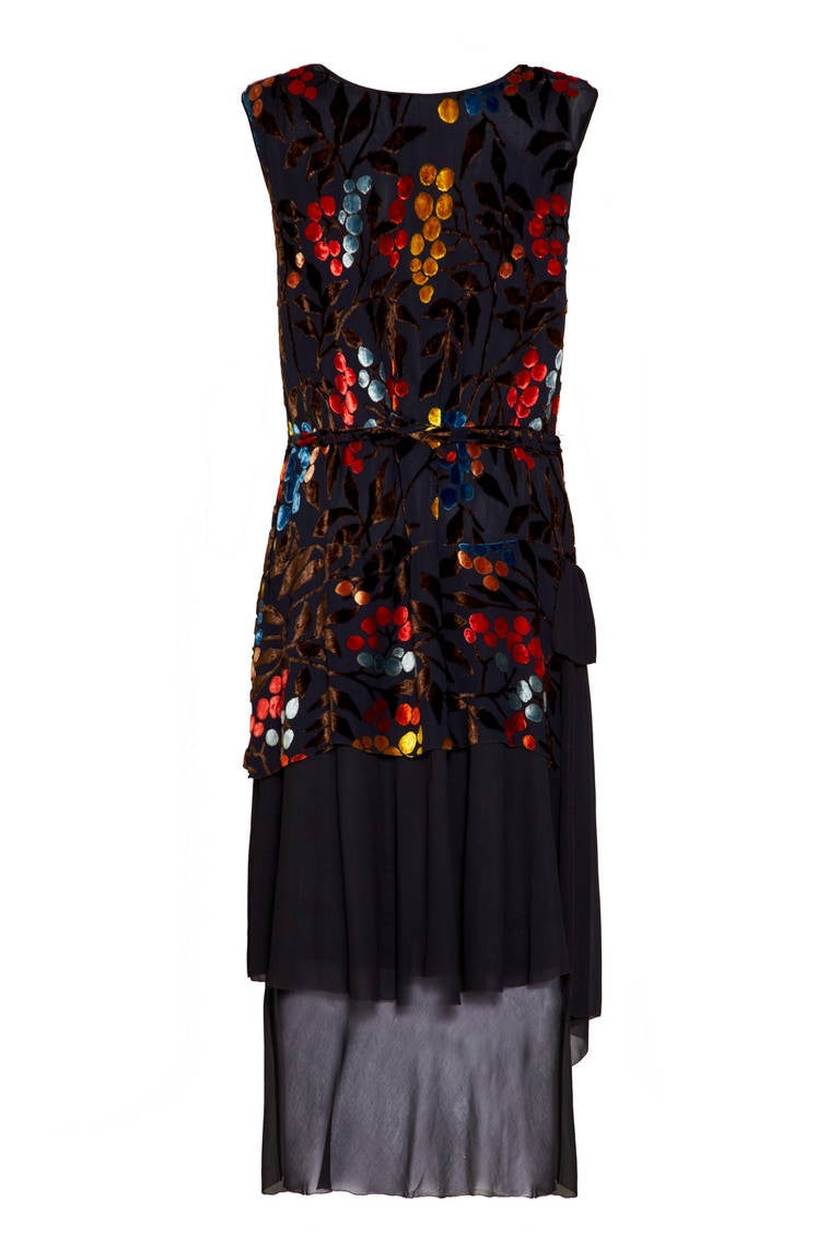 Sensational and rare multi-coloured burn out velvet flapper dress with a brown, yellow, orange and blue grape pattern on a black background. This sleeveless dress comes with original matching belt and (very delicate) black slip, which creates the