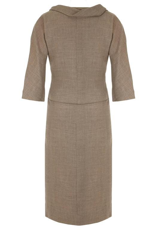 Beautiful and very stylish vintage 1960s Christian Dior New York soft grey wool dress suit.  This suit consists of a sleeveless dress with silk bodice and wool skirt and a jacket with 3/4 length sleeves which both fasten with an asymmetrical side