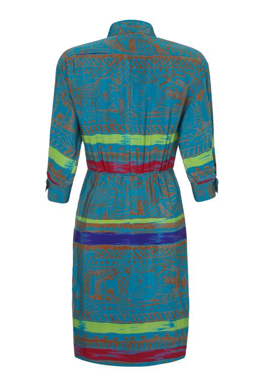 Cute vintage 1980s colourful batik style printed silk shirt dress by Jean- Louis Scherrer.  The main body of this dress is a deep turquoise with stripes of green, red and purple.  There are large turquoise buttons to fasten down the front, on the