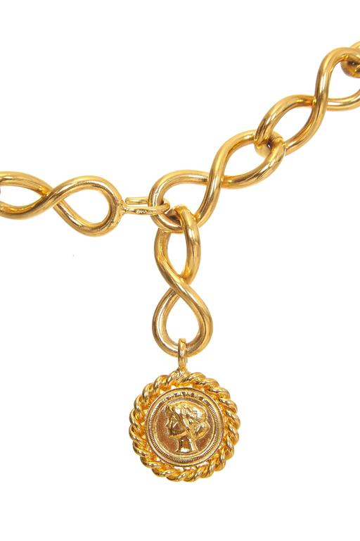 """Classic 1980s early 1990s vintage gold gilt metal Chanel belt with medallion charm featuring the head of Gabrielle """"Coco"""" Chanel at the end of the single chain which is made up of figure of eight links.  It fastens with a hook that can go in to any"""