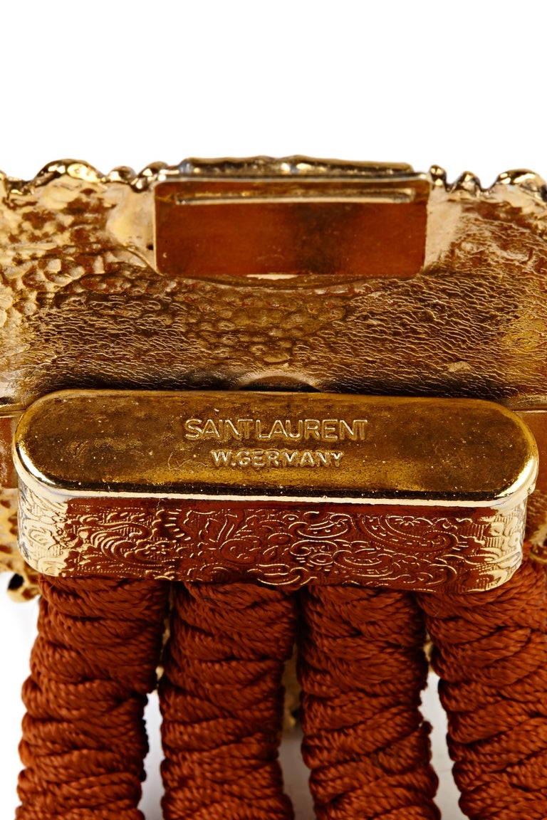 This unusual Yves Saint Laurent vintage belt is in superb condition and would add instant glamour to even the most understated ensemble. The belt is made up of four pieces of (pleasingly chunky), copper/ rust red elasticated cord, and is fastened by
