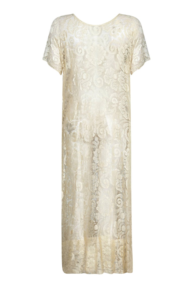 This enchanting vintage 1920s cream lace bridal dress is exquisitely feminine with an etherial, romantic feel. The dress is made up of delicate silk lace in soft cream, with a subtle glossimer effect that shimmers slightly in the light to capture