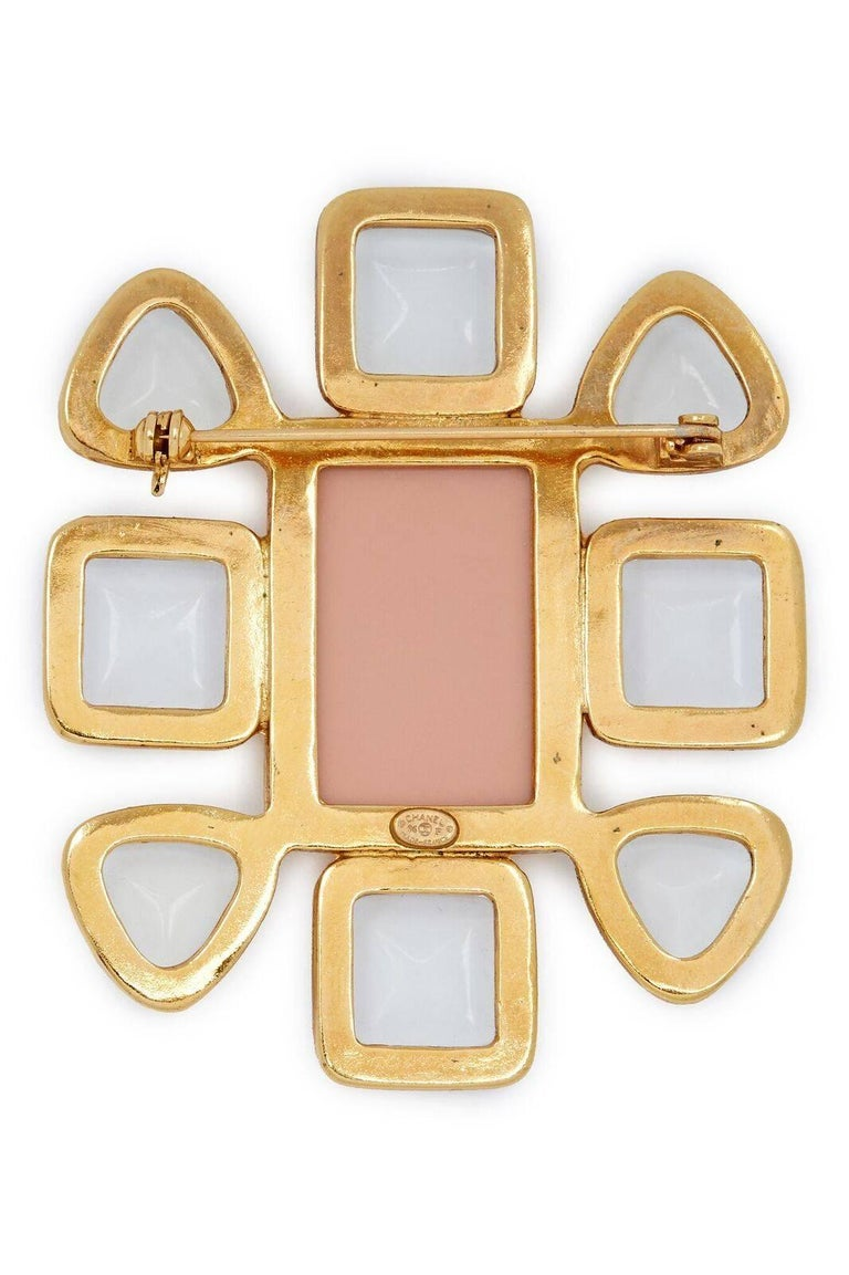 Gold-tone Chanel brooch featuring clear glass (gripoix) cabochons, rose enamel centrepiece with a small double CC affixed to the centre. C clasp pin closure. From the Spring 1996 Collection.   In excellent vintage condition.  2 1/4 inches/6.5cm wide