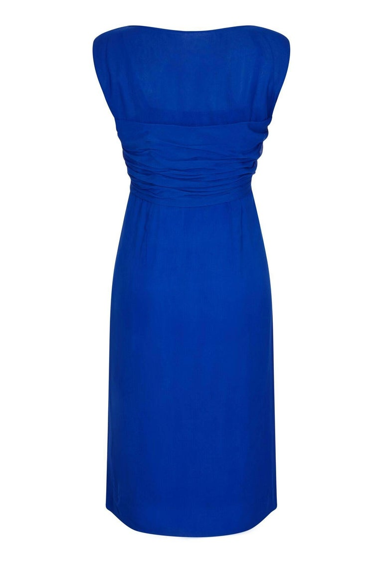 This charming 1950s silk chiffon evening dress in cobalt blue has been beautifully constructed to haute couture standard and is in pristine vintage condition. The chiffon overlay is exquisitely tailored to showcase a sleeveless hourglass silhouette.