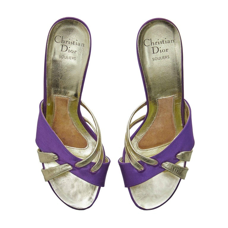 These exquisite 1970s Christian Dior heeled sandals with cross toe detail are beautifully made and in impeccable condition. There is a 3 inch cone heel with open back and toes. Rich purple satin fabric crossing with a gold tone leather double strap
