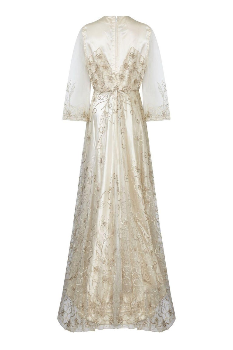 This enchanting late 1950s wedding dress in warm ivory with delicate floral embroidery is in superb condition and has a simple feminine silhouette. The thick sateen underlay is a sleeveless shift cut with a modest round neck, neatly synched at the