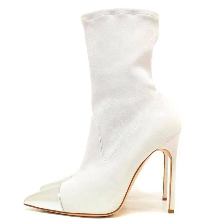 Manolo Blahnik cream pointed sock boots with patent leather silver toe detail and exposed stitching.