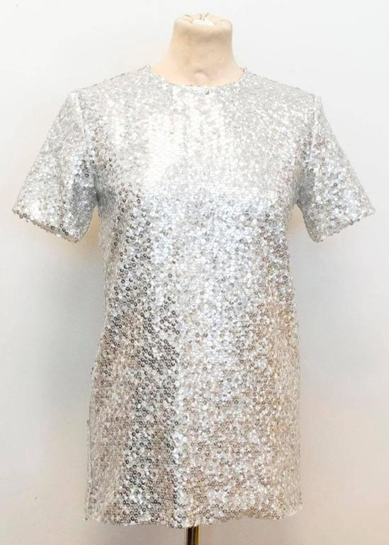 Nina Ricci silver sequined voile t-shirt top. This t-shirt is long in length and features a silk-polyester blend lining as well as an invisible zip at the back of the top.  There are some missing sequins on the item's sleeve and bottom hem, (please