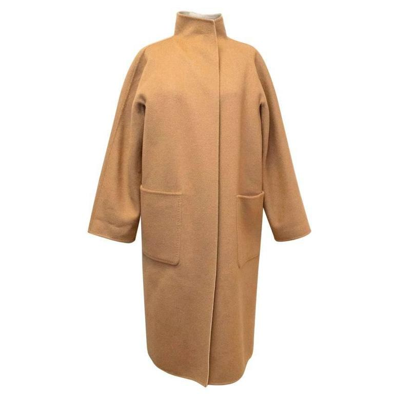 MaxMara tan and beige reversible coat. The coat is medium-weight and soft to the touch with an oversized fit. Featuring four functioning pockets, two on each side, and long sleeves, the coat does not fasten and comes with a reversible belt.  Size US
