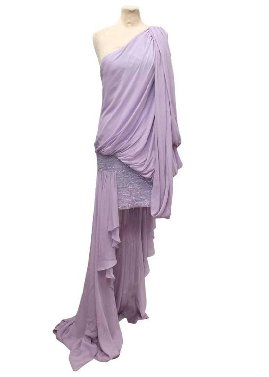 Elie Saab lilac one shoulder silk dress featuring a beaded, embellished mini skirt and a draped waterfall train with embellished detail on the shoulder and draping detail to the shoulder, hips and back. The dress is light weight and soft to the