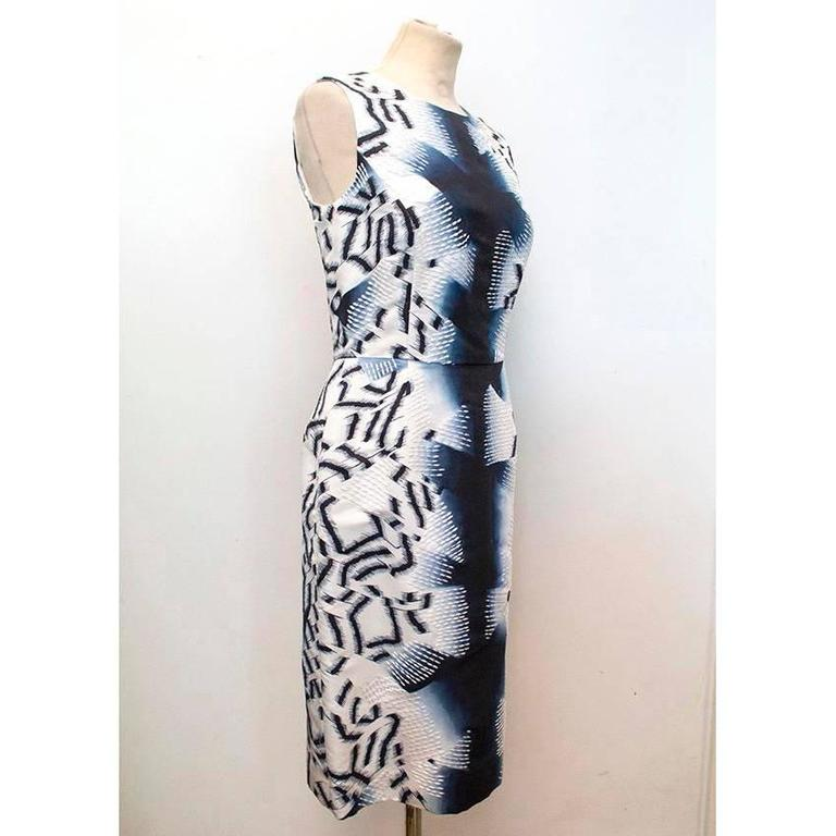 Oscar de la Renta abstract print sleeveless silk dress with white embroidery. Fitted style that is cinched at the waist with soft boat neckline.