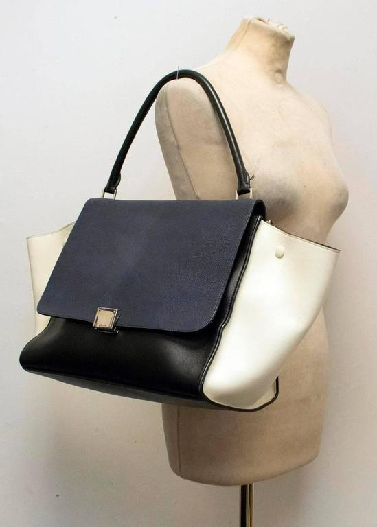Celine Trapeze bag in black, white and navy featuring black suede lining and silver hardware, single top handle, flap front and zipped pocket to the back.