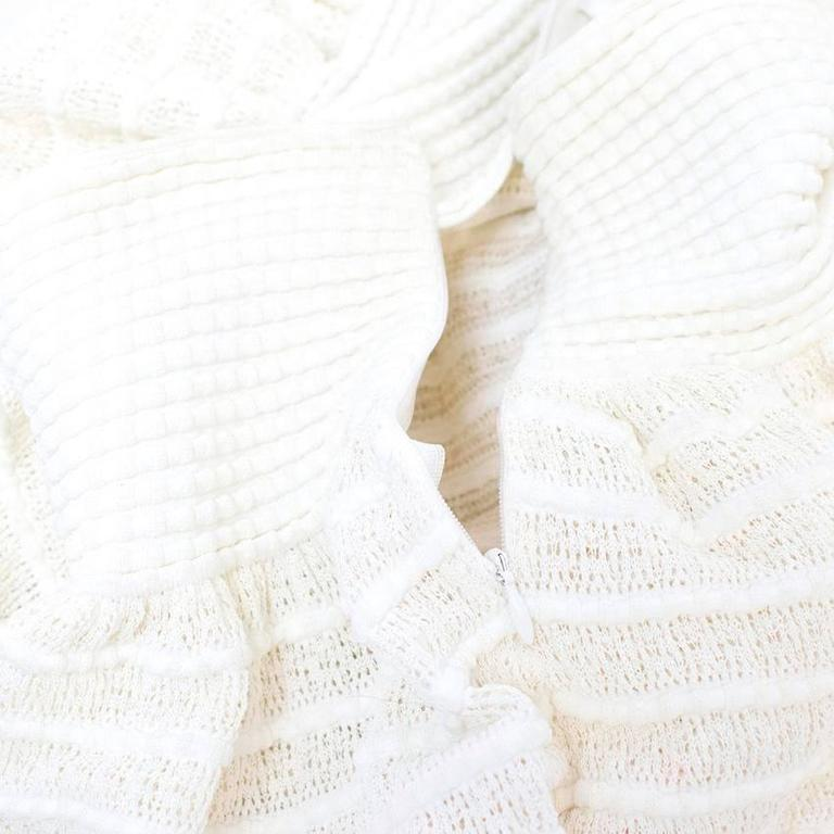 Alaia cream coloured short skater skirt with textured horizontal stripes and a full skirt. Fastens on the side with a concealed zipper and a metal hook at the top.   There are minor marks on the lining near the zip that won't be visible when