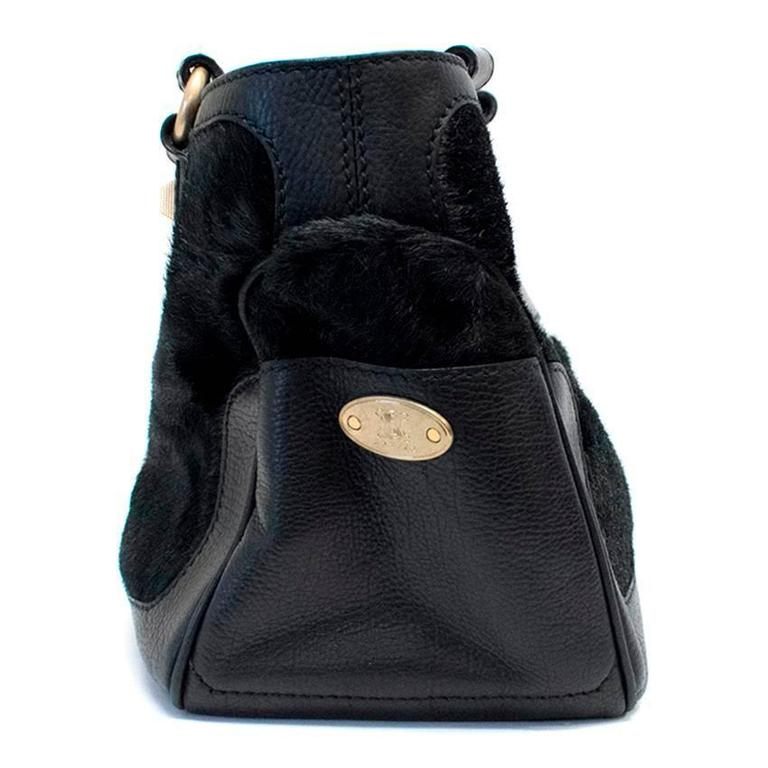 Celine black ponyhair tote bag with gold hardware and black leather accents along the bottom sides, and handles. There are two side pockets as well as a large interior zipper pocket and a smaller compartment on the interior side.  Minimal wear to