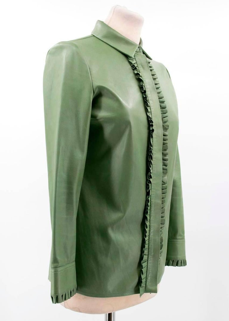 Gucci green leather top.   Button-down top in soft green leather featuring frilled detailing. Made in Italy.   Conditions Details : Condition - 9/10   Some minor marks and signs of wear to leather.   Please note, these items are pre-owned and may