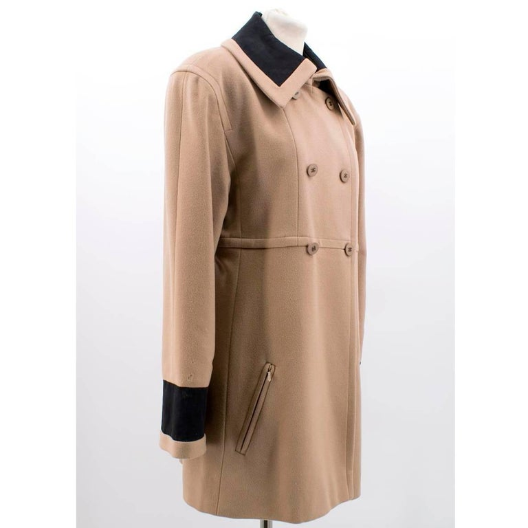 Chanel tan wool coat in a double-breasted '60's collared style featuring Chanel logo buttons and black panels.   Size: US 6 Measurements: Approx. Bust: 48cm Waist: 47cm Length: 83cm Sleeve: 60cm Conditions Details : 8.5/10. Signs of wear at back