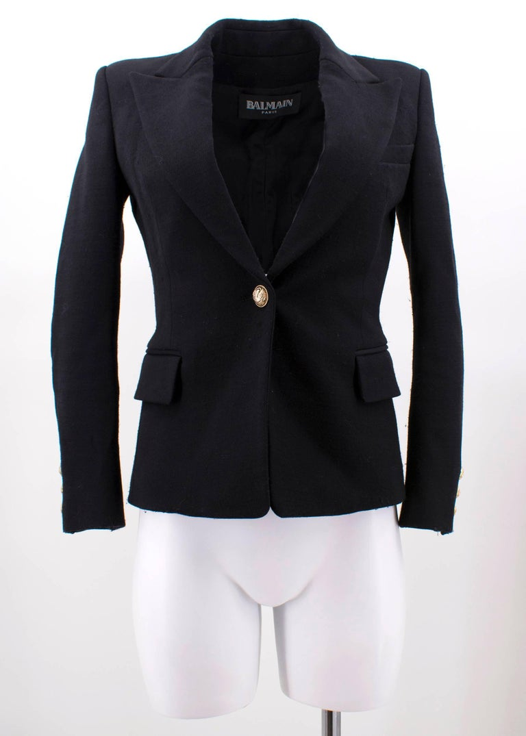 Balmain black wool blazer featuring padded shoulders, one button fastening through front, two flap pockets, one slit pocket and gold-tone embossed button.  Fabrics: 96% Wool, 2% Elastan and 2% Polyamide.  Approx Measurements:  Shoulders- 38cm