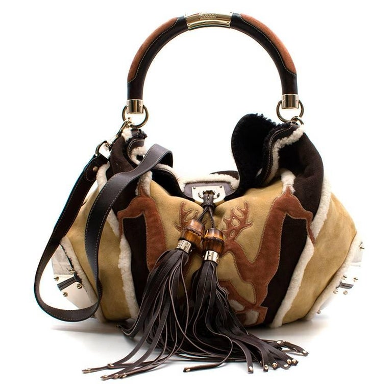Gucci Shearling Large Indy Bag.  Beige and multicolor shearling Gucci Large Indy hobo with gold-tone hardware, leather trim, rounded top handle, tassel accents, tonal shearling interior and weighted closure at front. Includes leather zip