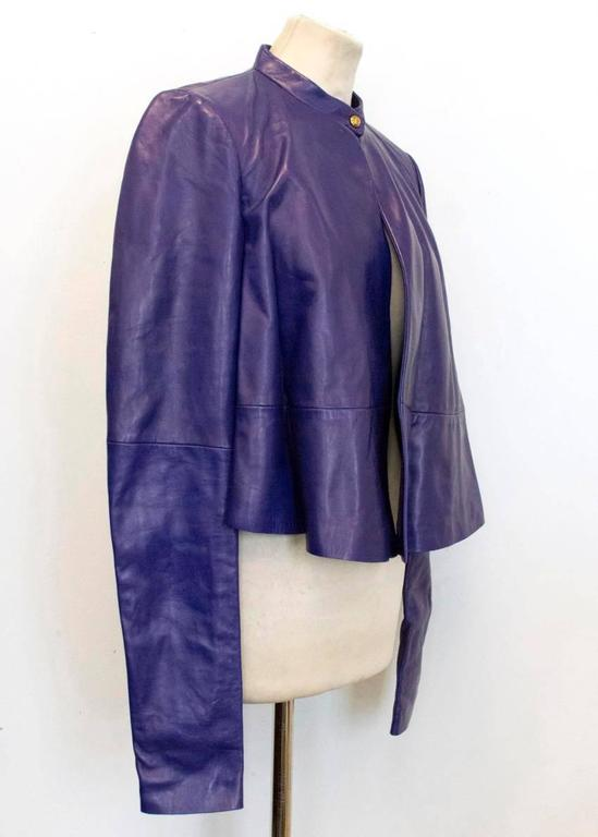 Vionnet purple fully lined leather bomber with a round neck, long sleeves, high neck single gold snap button closure, paneling detail on the back and a slightly lower back. Made in Italy. Size 40