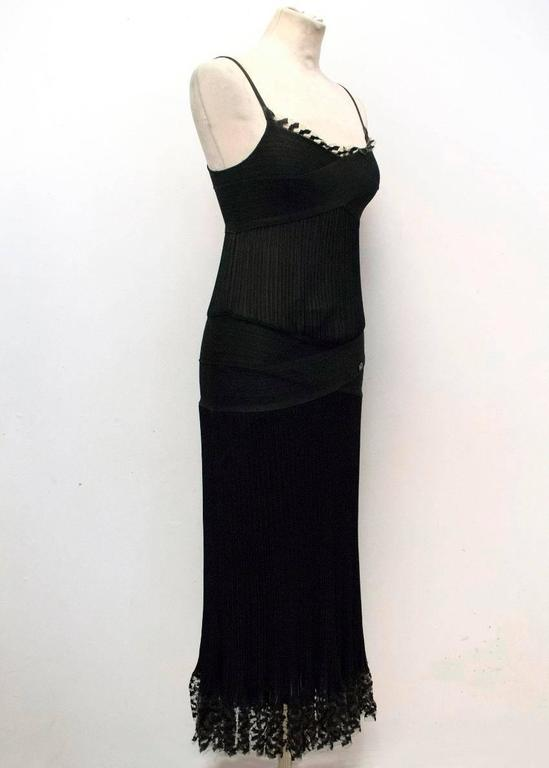 Chanel black, fitted, mid-length dress with thin shoulder straps and a ribbed, semi sheer design. It also features a lace trim on the hem and the neckline. 