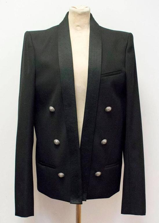 Balmain black, medium weight, military style jacket with a ribbed shawl lapel and gunmetal buttons. It features three exterior pockets and two interior pockets. Please note that it is an open jacket and cannot be done up. 
