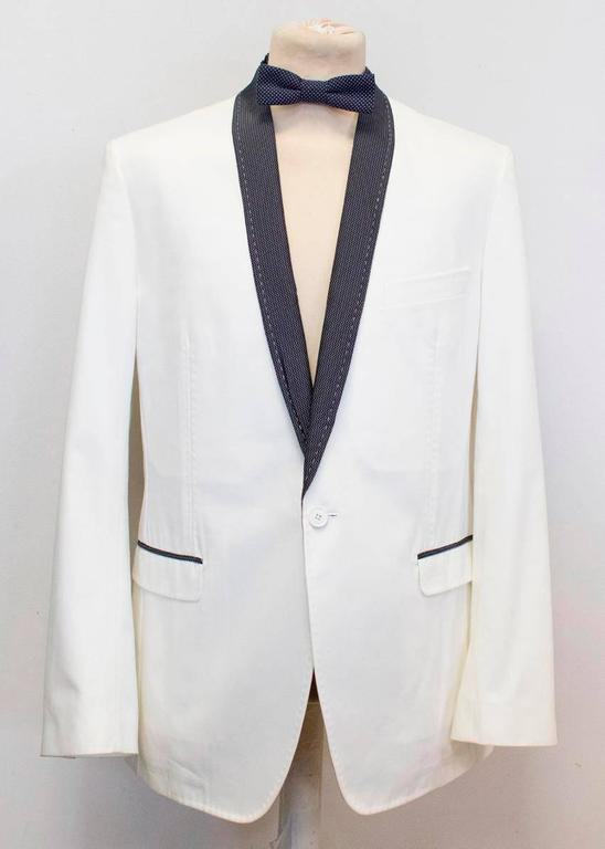 Dolce and Gabbana white dinner jacket with black polka dot lapels featuring:  - a shawl lapel  - three exterior pockets - two interior pockets - one vent - one front button - four button cuffs - partially lined   Comes with a matching polka bow tie.