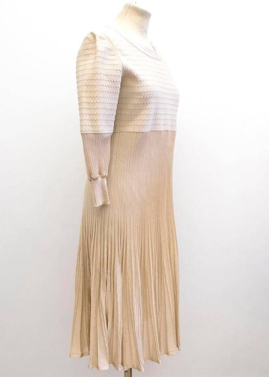 Chanel nude long sleeved, pleated dress.  There are three cream buttons on the left shoulder, which feature the chanel emblem. The dress is mid length.  Please note, these items are pre-owned and may show signs of being stored even when unworn and