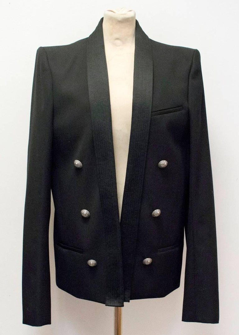 Balmain black blazer jacket, double breasted, shawl lapels and 2 button cuffs. The blazer also features 3 non-functioning pockets, shoulder pads and silver embossed buttons.  Condition: 10/10  Fabric: Body: 100% Wool/ Fabric 2: 57% Cotton/ 43% Silk/