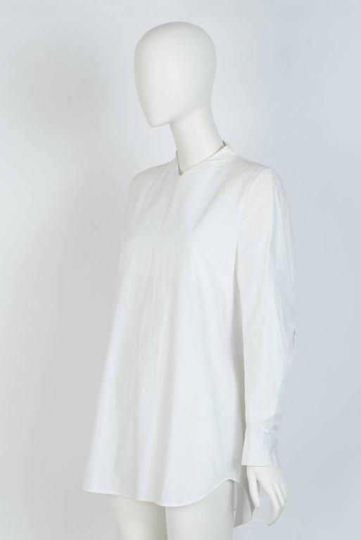 Structured, collarless blouse in white cotton  with shoulder padding and buttoned cuff..