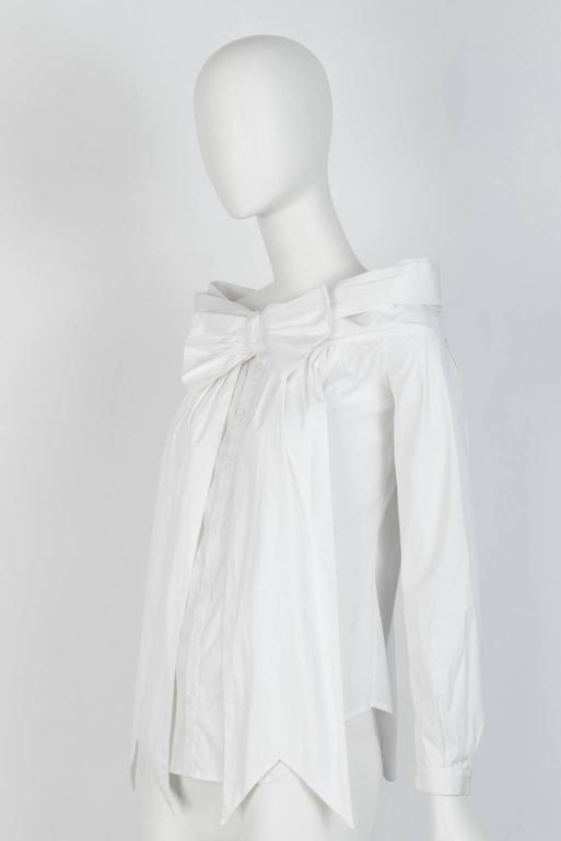 Pleated, open shoulder white cotton top with sashed bow tie front.