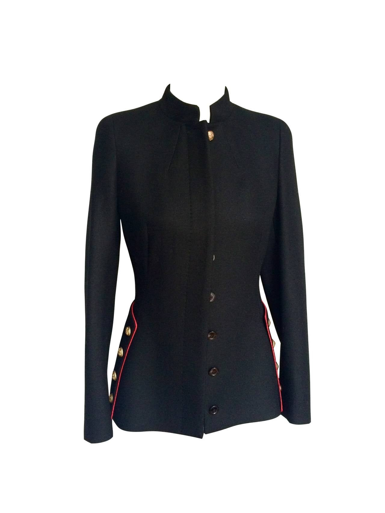 A brandnew emblematic piece from Pre-Fall 2011 designed by the talented Sarah Burton for Alexander McQueen. Inspired by Manet, with a military twist, this black wool jacket features a red braid and eight emblazoned golden buttons on the side. Ten