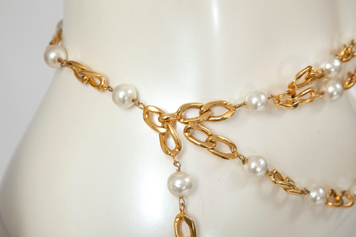 Simply chic vintage Chanel triple gold plated chain belt with faux pearls. Multi strand pink faux mini pearls tassel ornament hangs at the end of the pendant chain. Hook closure. Adjustable length.  Measurements (taken flat) : Full length (end to