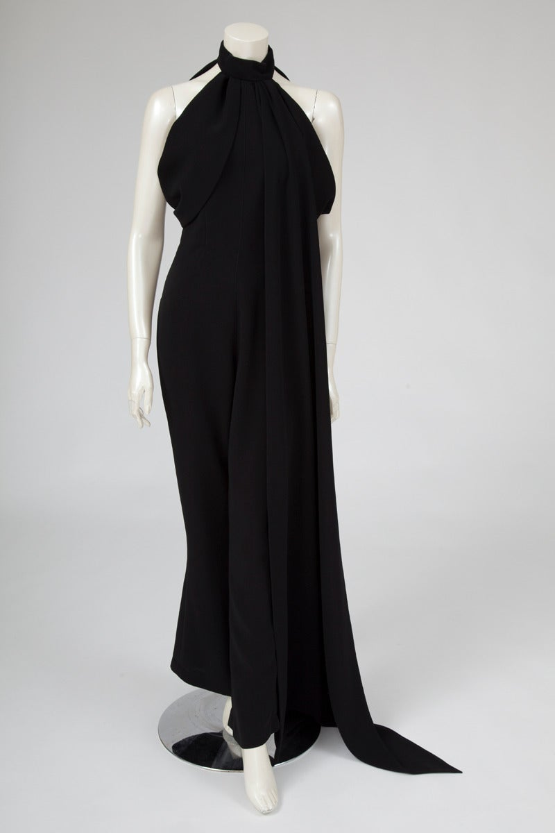 Late 80's - early 90's rare and collectible example of Thierry Mugler's sculptural designs, this black jumpsuit is still very modern, chic and wearable. Incredible draping and cut, it closes with a zip at the back. Attached in front of the left side