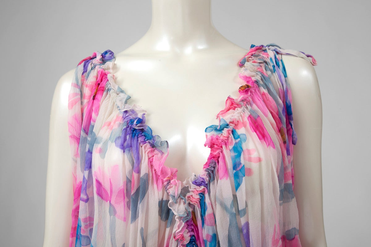 70's enchanting and colorful Jean Patou caftan-dress. The flower print features a delicious combination of light purple, gray, turquoise, neon pink and fuchsia. The caftan can be adjusted or tightened thanks to a matching silk chiffon cord at the