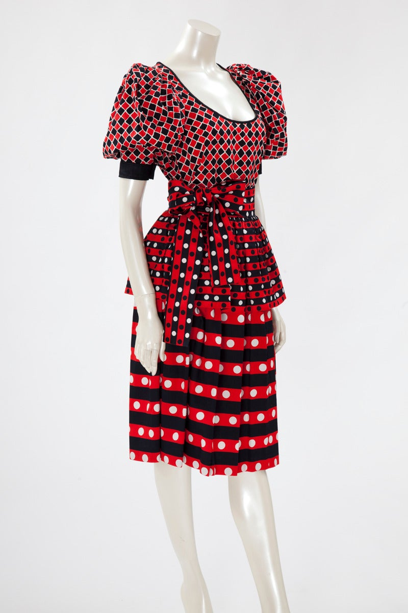 Emblematic YSL Harlequin print top, skirt and matching belt. Contrasted with the skirt in the same red, jet black and white colours, the top has a scoop neckline and a black cotton yoke, closing with a button, at the end of the puff sleeves. There